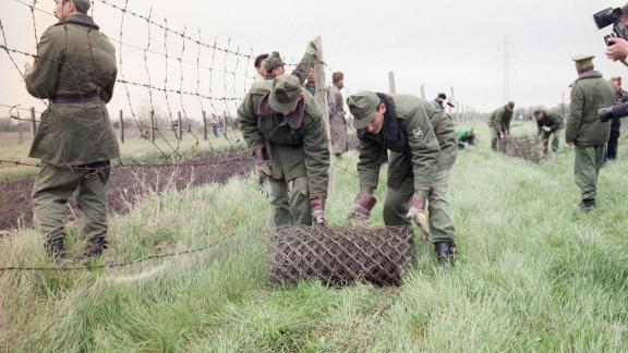 "Hungarian border guards begin dismantling the ""Iron Curtain"" in May 1989, opening the country"