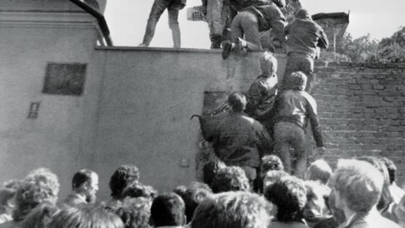 East German citizens scale the walls of the West German embassy in Prague in October 1989, in a desperate first step to freedom.