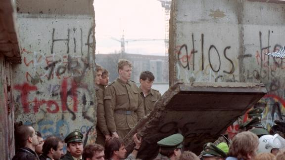 East German border guards appear in a gap in the Wall after demonstrators pulled down a segment of the barrier, on November 11, 1989.