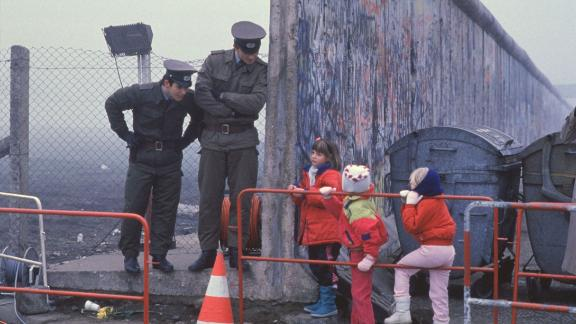 West German children interact with East German border guards after the fall of the Berlin Wall in 1989.
