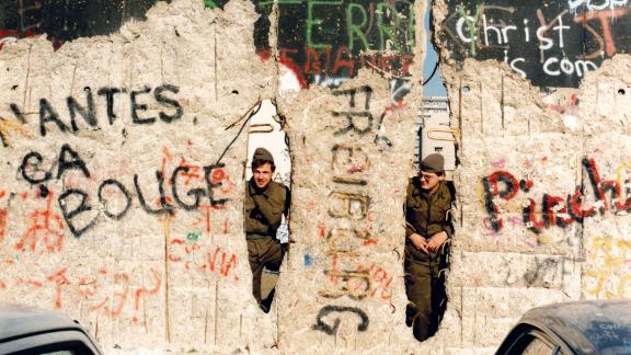 East German border guards peer through the damaged wall, near Checkpoint Charlie, in February 1990.