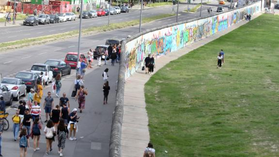 People walk along the longest remaining section of the Wall, now known as the East Side Gallery, in August this year.