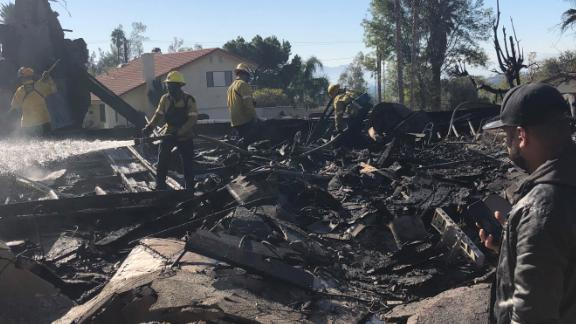 Matthew Valdivia stands in front of the burned wreckage of his house in San Bernardino.