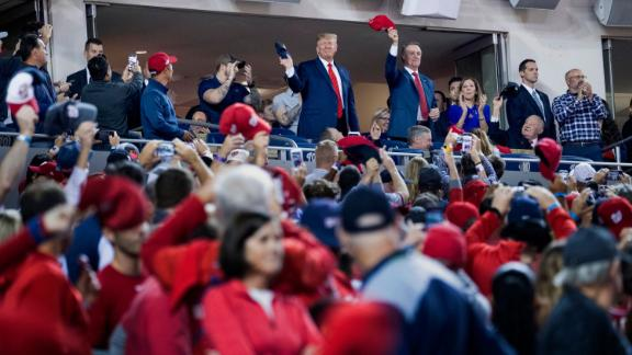 President Donald Trump, center, accompanied by Sen. David Perdue, R-Ga., right, stands as members of the military are recognized during Game 5 of a baseball World Series between the Houston Astros and the Washington Nationals at Nationals Park in Washington, Sunday, Oct. 27, 2019. (AP Photo/Andrew Harnik)