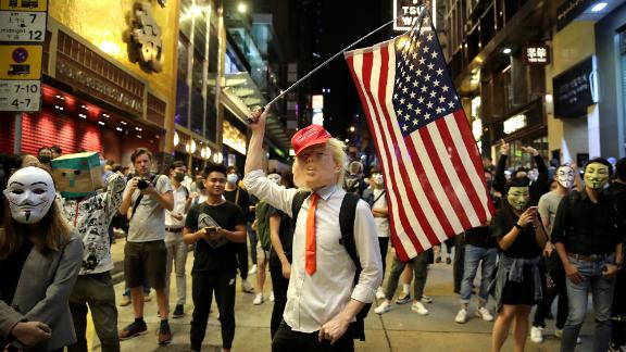 A person dressed as President Donald Trump waves an American flag on a street in Hong Kong on Thursday, October 31, 2019. Hong Kong authorities braced as pro-democracy protesters urged people on Thursday to celebrate Halloween by wearing masks on a march in defiance of a government ban on face coverings.