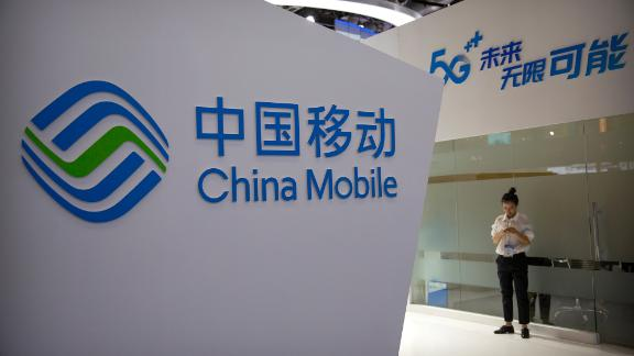 A woman uses her smartphone at a display for 5G services from China Mobile at the PT Expo in Beijing, Thursday, Oct. 31, 2019. The government-organized event comes amid a trade dispute with Washington in part over China's plans for the state-led championing of its own global technology competitors. (AP Photo/Mark Schiefelbein)