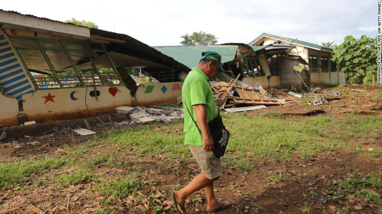 A resident walks past a collapsed school building after a 6.6-magnitude earthquake hit Tulunan town, North Cotabato province, on the southern island of Mindanao on October 29, 2019.