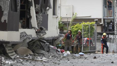 Rescuers look at the damaged condominium building after a 6.5-magnitude earthquake hit Davao City in the southern island of Mindanao on October 31, 2019.