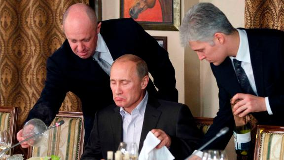 FILE - In this Friday, Nov. 11, 2011 file photo, businessman Yevgeny Prigozhin, left, serves food to Russian Prime Minister Vladimir Putin, center, during dinner at Prigozhin's restaurant outside Moscow, Russia. Ten years ago, he served plates to President Vladimir Putin. These days, St. Petersburg-based businessman Yevgeny Prigozhin funds Kremlin trolls and sends mercenaries to help Russia's military operation in Syria _ all with one aim: to do the president favors that would be too risky for other Russian moguls to undertake. (AP Photo/Misha Japaridze, Pool, File)