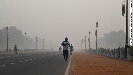 A man jogs along a street under smoggy conditions in New Delhi on November 1, 2019.