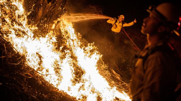 Firefighters spray water on a backfire while battling the spread of the Maria Fire on Friday, November 1. It is just one of the numerous wildfires in California right now.