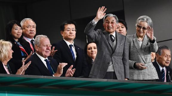 Japan's former Emperor Akihito (centre L) and Empress Michiko wave during the bronze final match.