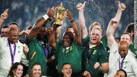 South Africa's President Cyril Ramaphosa (centre R) and Kolisi (centre L) lift the trophy.