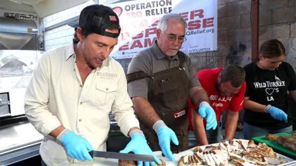 Matthew McConaughey helping prepare barbecue for firefighters battling California's wildfires on Friday.