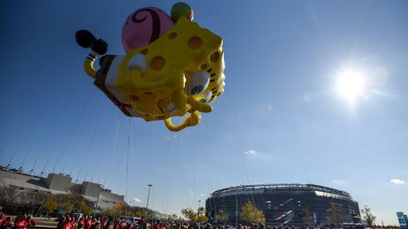 A SpongeBob SquarePants and Gary balloon flies in front of Metlife Stadium