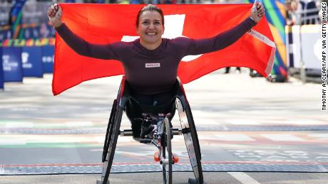 Manuela Schar holds the Swiss flag high after winning a third consecutive marathon in New York.