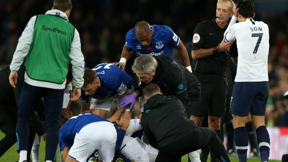 Match referee Martin Atkinson consoles Son Heung-Min as Everton players and medical staff cluster around the stricken Andre Gomes.