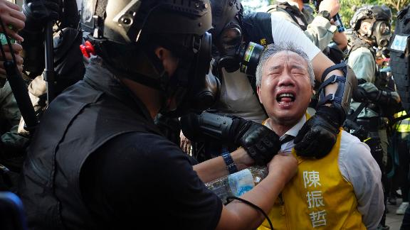 Richard Chan, a candidate for the district council elections, reacts after being pepper-sprayed by police in Hong Kong on November 2.