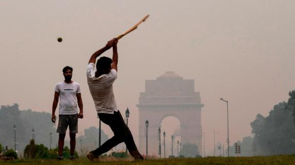 Youths play cricket in a park near India Gate under heavy smog in New Delhi on October 29.
