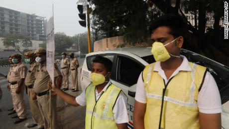 Volunteers and police wearing pollution masks instruct drivers to obey odd and even day rules to help reduce traffic emmisions and smog in New Delhi on Monday, November 4.