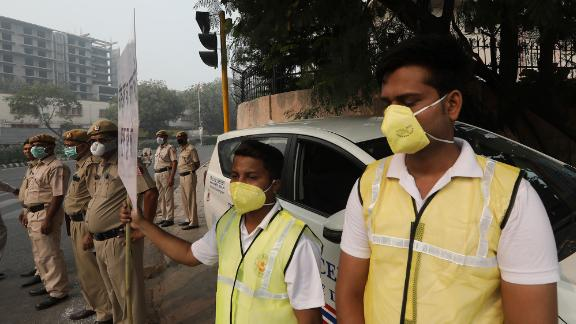 "Volunteers and police wearing masks hold a banner urging drivers to obey the ""odd-even"" scheme."