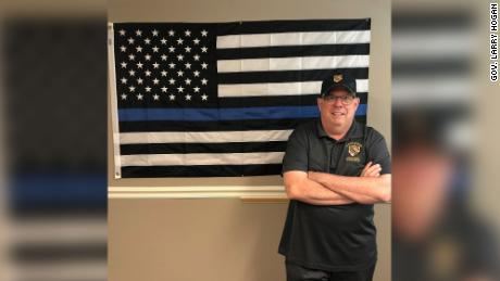 Gov. Larry Hogan poses with what he calls a thin blue line.