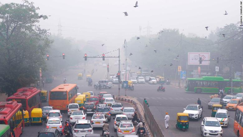 Vehicles wait at a traffic light amid heavy morning smog in New Delhi on Sunday, November 3.