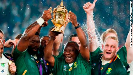 South Africa's President Cyril Ramaphosa (centre R) and South Africa's flanker Siya Kolisi (centre L) lift the Webb Ellis Cup as they celebrate winning the Japan 2019 Rugby World Cup final match between England and South Africa at the International Stadium Yokohama in Yokohama on November 2, 2019. (Photo by Odd ANDERSEN / AFP) / The erroneous mention[s] appearing in the metadata of this photo by Odd ANDERSEN has been modified in AFP systems in the following manner: [South Africa's President Cyril Ramaphosa] instead of [South Africa's hooker Bongi Mbonambi]. Please immediately remove the erroneous mention[s] from all your online services and delete it (them) from your servers. If you have been authorized by AFP to distribute it (them) to third parties, please ensure that the same actions are carried out by them. Failure to promptly comply with these instructions will entail liability on your part for any continued or post notification usage. Therefore we thank you very much for all your attention and prompt action. We are sorry for the inconvenience this notification may cause and remain at your disposal for any further information you may require. (Photo by ODD ANDERSEN/AFP via Getty Images)