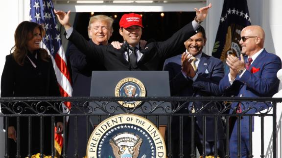 President Donald Trump stands with Washington Nationals catcher Kurt Suzuki, during an event to honor the 2019 World Series champion Washington Nationals on the balcony of the White House, Monday, November 4, in Washington, as First Lady Melania Trump, left, and Washington Nationals coach Dave Martinez, second from right and general manager Mike Rizzo, far right, look on. Suzuki is wearing a Make America Great Again hat.