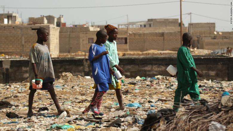 Mamadou, on the far left, with other talibés at the garbage dump which houses his Quranic school, in a part of Saint Louis called Darou.