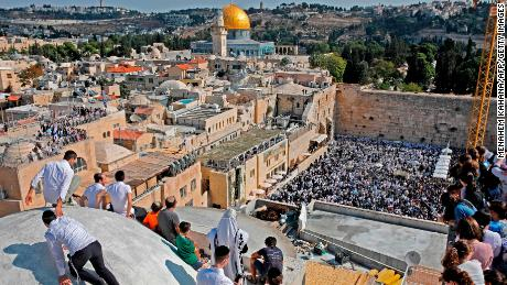 People gather at the Jewish quarter in the old city of Jerusalem as worshippers perform the annual Birkat Kohanim (Priestly Blessing) during the Sukkot holiday, or the feast of the Tabernacles, at the Western Wall (bottom) on October 16, 2019. - Thousands of Jews make the pilgrimage to Jerusalem during Sukkot, which commemorates the desert wanderings of the Israelites after their exodus from Egypt. (Photo by Menahem KAHANA / AFP) (Photo by MENAHEM KAHANA/AFP via Getty Images)