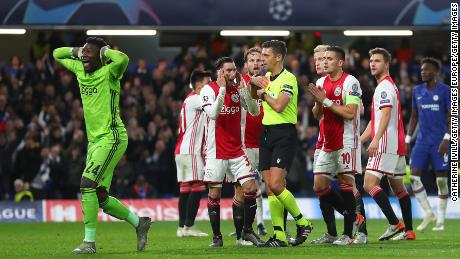 Ajax players react after the referee sends off two players and awards Chelsea a penalty.