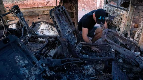 "A member of the Lebaron family looks at the burned car where part of the nine murdered members of the family were killed and burned during an ambush in Bavispe, Sonora mountains, Mexico, on November 5, 2019. - US President Donald Trump offered on November 5 to help Mexico ""wage war"" on its cartels after three women and six children from an American Mormon community were murdered in an area notorious for drug traffickers. (Photo by HERIKA MARTINEZ / AFP) (Photo by HERIKA MARTINEZ/AFP via Getty Images)"