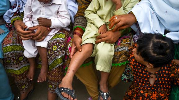 In this image taken on May 8, 2019, Pakistani women hold their HIV infected children as they gather at a house at Wasayo village in Ratodero in the district of Larkana of the southern Sindh province.