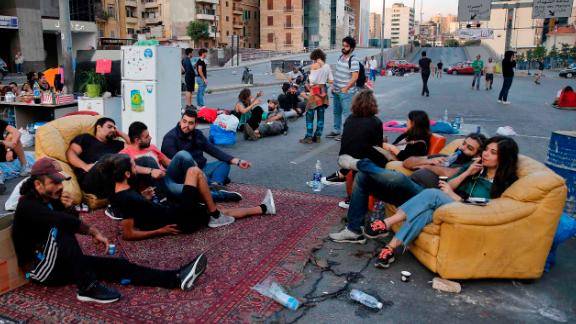 Anti-government protesters sit in the middle of a highway during ongoing protests against the government in Beirut, Lebanon, Monday, Oct. 28, 2019. The protests have paralyzed a country already grappling with a severe fiscal crisis at reinforcing calls for the government to step down as nationwide protests entered their 12th day Monday. (AP Photo/Hussein Malla)