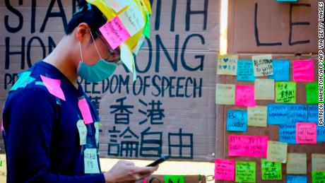 "This photo taken on August 9, 2019 shows a supporter of the Hong Kong pro-democracy protests, seen covered in sticky notes, standing in front of a makeshift ""Lennon Wall"" at the University of Queensland in Brisbane, Australia."