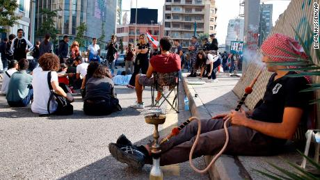 An anti-government protester smokes a water pipe as others block a main highway in Beirut on November 4.