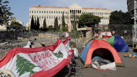 Lebanese protesters sleep in tents in front of the government headquarters, known as the Grand Serail building, in Beirut on October 25.