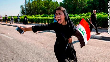 An Iraqi girl holding a national flag and a cell phone chants at a demonstration outside the port of Umm Qasr on November 5.