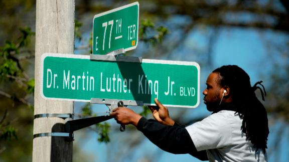 A worker installs a Dr. Martin Luther King Jr. Blvd. sign in Kansas City in April, 2019.