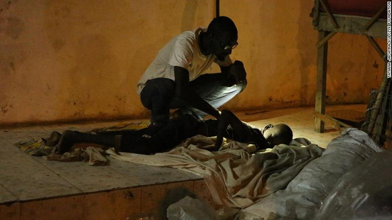 A member of Kouyate's team checking on a boy sleeping in the street.