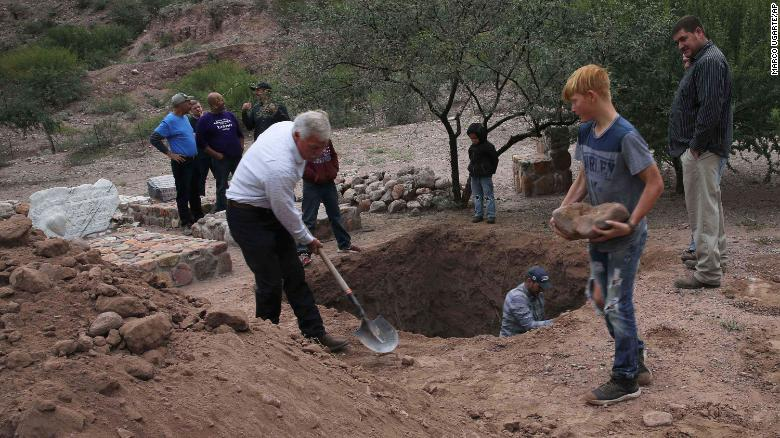 Men dig a mass grave in La Mora on Thursday for some of the women and children who were killed in Monday's massacre.