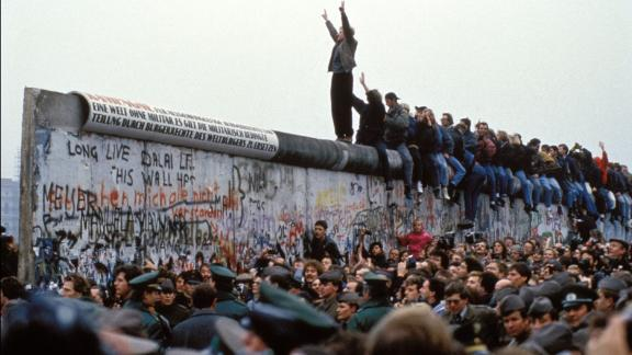 BERLIN, GERMANY - NOVEMBER 12: A man celebrates on the Berlin wall on November 12, 1989 in Berlin, Germany.(Photo by Pool CHUTE DU MUR BERLIN/Gamma-Rapho via Getty Images)