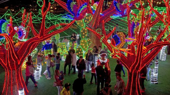 People attend the Christmas lights illumination in the Medellin river on December 1, 2012 in Medellin, Antioquia department, Colombia.