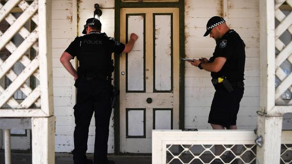 Police knock on the door of a house to warn residents of an out-of-control bushfire near Clumber on November 8.