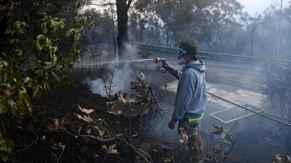 A resident hoses smoldering logs as a bushfire burns in Woodford on November 8.