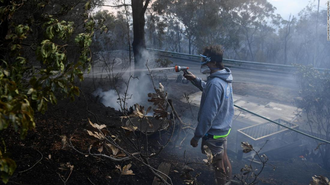 A resident hoses smoldering logs as a bushfire burns in Woodford, New South Wales, on November 8.