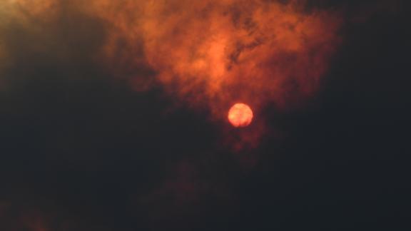 The sun is seen through heavy smoke as a bushfire burns in Woodford.