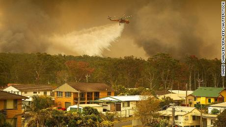 A water bombing helicopter drops water on a bushfires in Harrington, New South Wales, Australia, 08 November 2019.