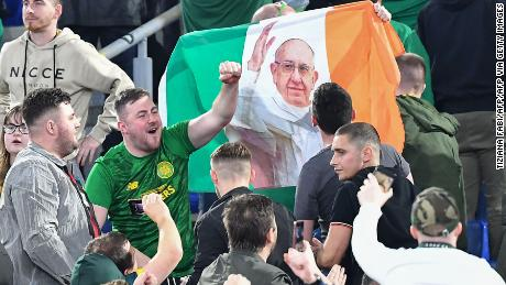 Celtic fans wave the flag of Ireland with a photo of Pope Francis.